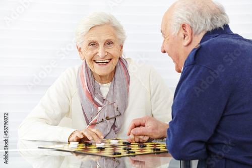 Happy senior couple playing checkers