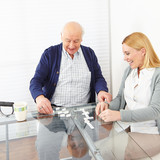 Woman playing domino with senior man