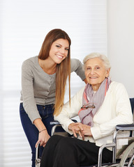 Young woman and senior citizen in wheelchair