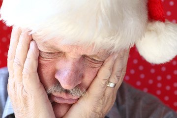 man looks sad in Santa hat