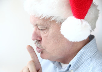 man in Santa hat with hush gesture