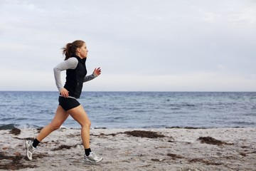 Fit and healthy young woman running along shoreline
