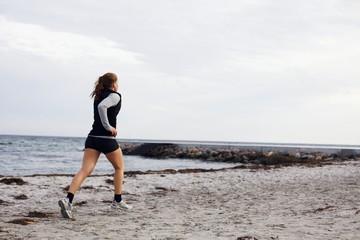 Young female runner running on beach