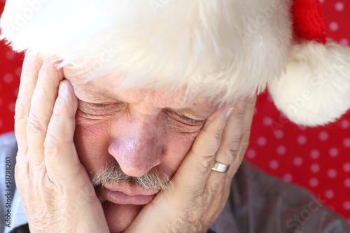 man looks sad in Santa hat