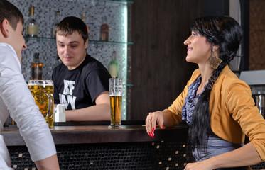 Barman socialising with customers at the bar