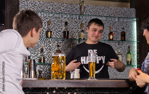 Barman serving customers at the bar counter