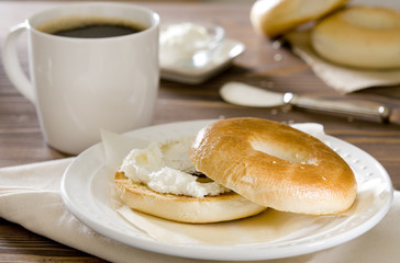 cup of coffee and a toasted bagel with cream cheese.