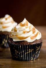 Closeup of two salted caramel chocolate cupcakes.