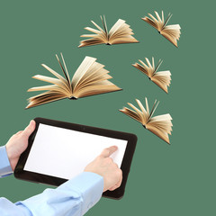 Tablet and opened books on green background