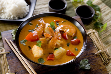 bowl of red thai curry with scallops, shrimp and vegetables.