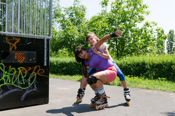 Two rollerbladers practising at the skate park