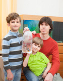 Father and two boys hold packet with propical fish