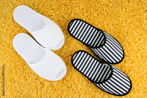 Striped and white slippers on carpet background