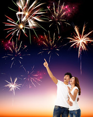 happy young couple watching the fireworks in the sky