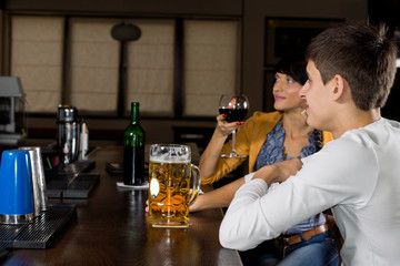 Young man next to his female friend at the bar