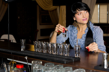 Woman drinking vodka shots at a bar