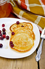 Flapjacks with cranberry in a plate on a board