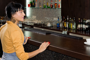 Young woman waiting for service at the bar counter