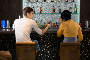 Young couple sitting drinking at the bar