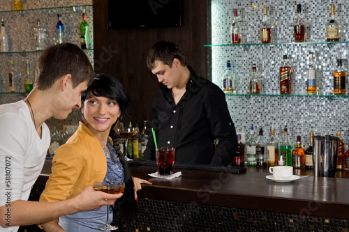 Young man chatting up a woman at the bar