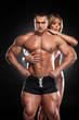 Sexy fit blond girl hugging from behind male bodybuilder.