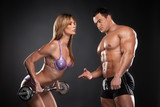 Sexy bodybuilder coach training beautiful fit blond woman.
