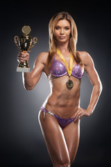 Attractive female bodybuilder holding cup and having medal.