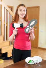 Happy red-haired girl warming shoes with hairdryer