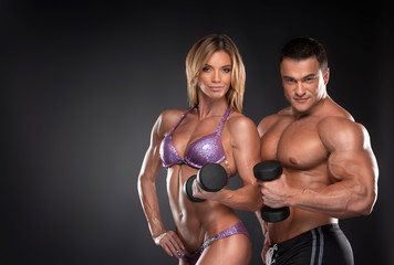 Couple of well trained bodybuilder with dumbbells. © BlueSkyImages