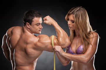 Sexy fit blond woman measure hand male  muscular.