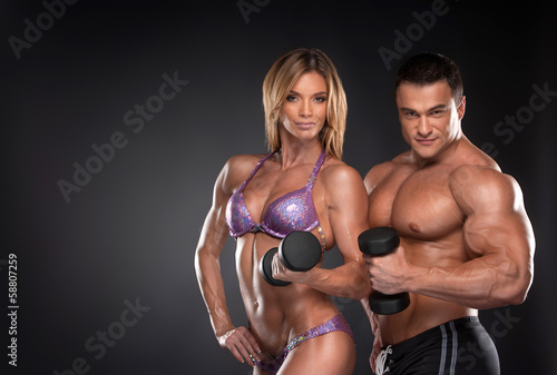 Couple of well trained bodybuilder with dumbbells.