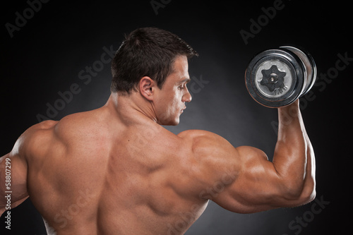 Back view muscular man lifting dumbbell up.