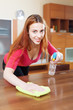 young woman dusting wooden table