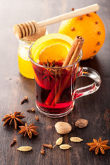 Hot Christmas drink (mulled wine) with spices, honey and orange