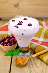 Yogurt thick with cranberries and spoon on the board
