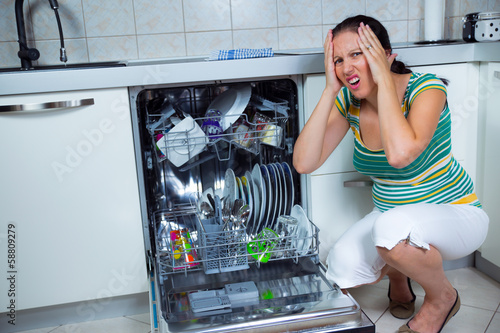 Woman sits near to the open dishwasher on kitchen