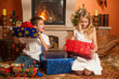Children with holiday gifts by fireplace