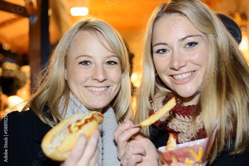 Frauen essen Pommes Frites und Bratwurst - 58810256