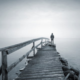 Man on the old broken wooden pier starring at the foggy Sea