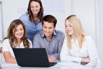 junge leute sitzen im büro und schauen auf laptop