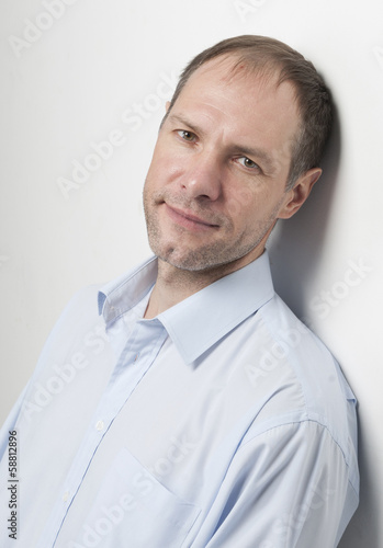 portrait of pensive man in blue against the wall