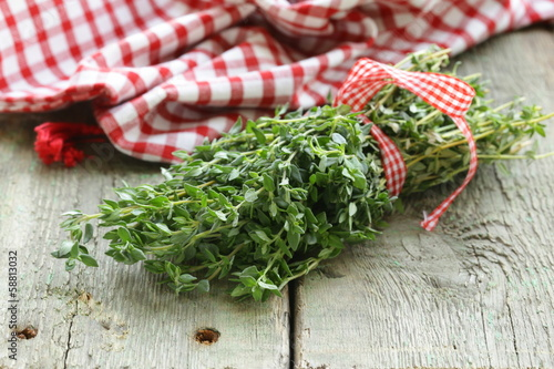 bunch of fresh green thyme on a wooden table