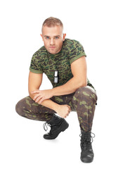 Portrait of young army soldier squatting