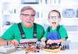 Happy grandfather and grandchild working in workshop
