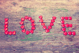 "The word ""love"" on a wooden background in grunge style"