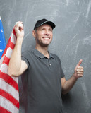 Smiling man in gray against background of the USA flag