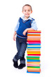 Little boy standing near stacked colorful books