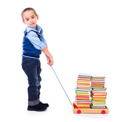 Little boy pulling books in toy cart