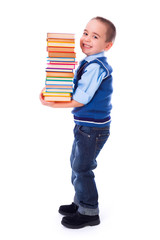 Little boy carrying stacked books