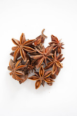 Star anise piled up on a white background.